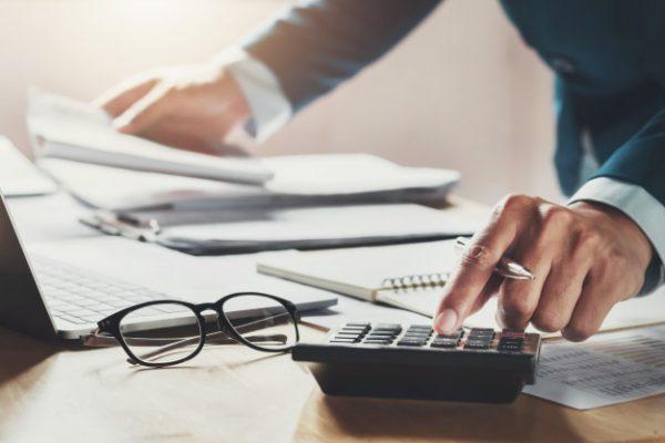 hombre-negocios-que-usa-calculadora-calcula-trabajo-oficina