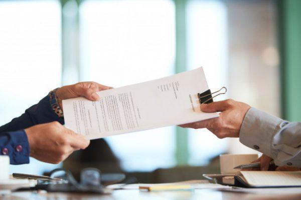 primer-plano-manos-pasando-contrato-proveedor-para-firmar